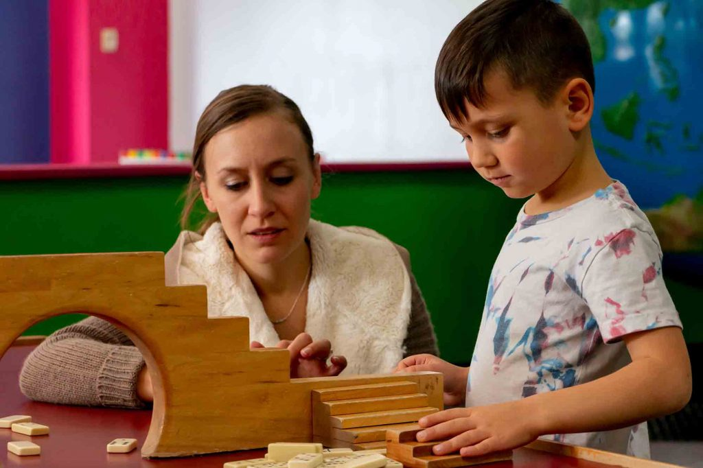 Mother and child playing with blocks and dominoes